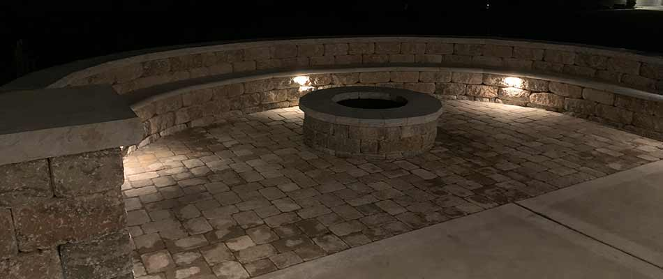 A paver patio and custom fire pit at night with landscape lighting in Columbia, IL.